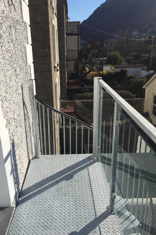 Glass balustrade landing on spiral stairs