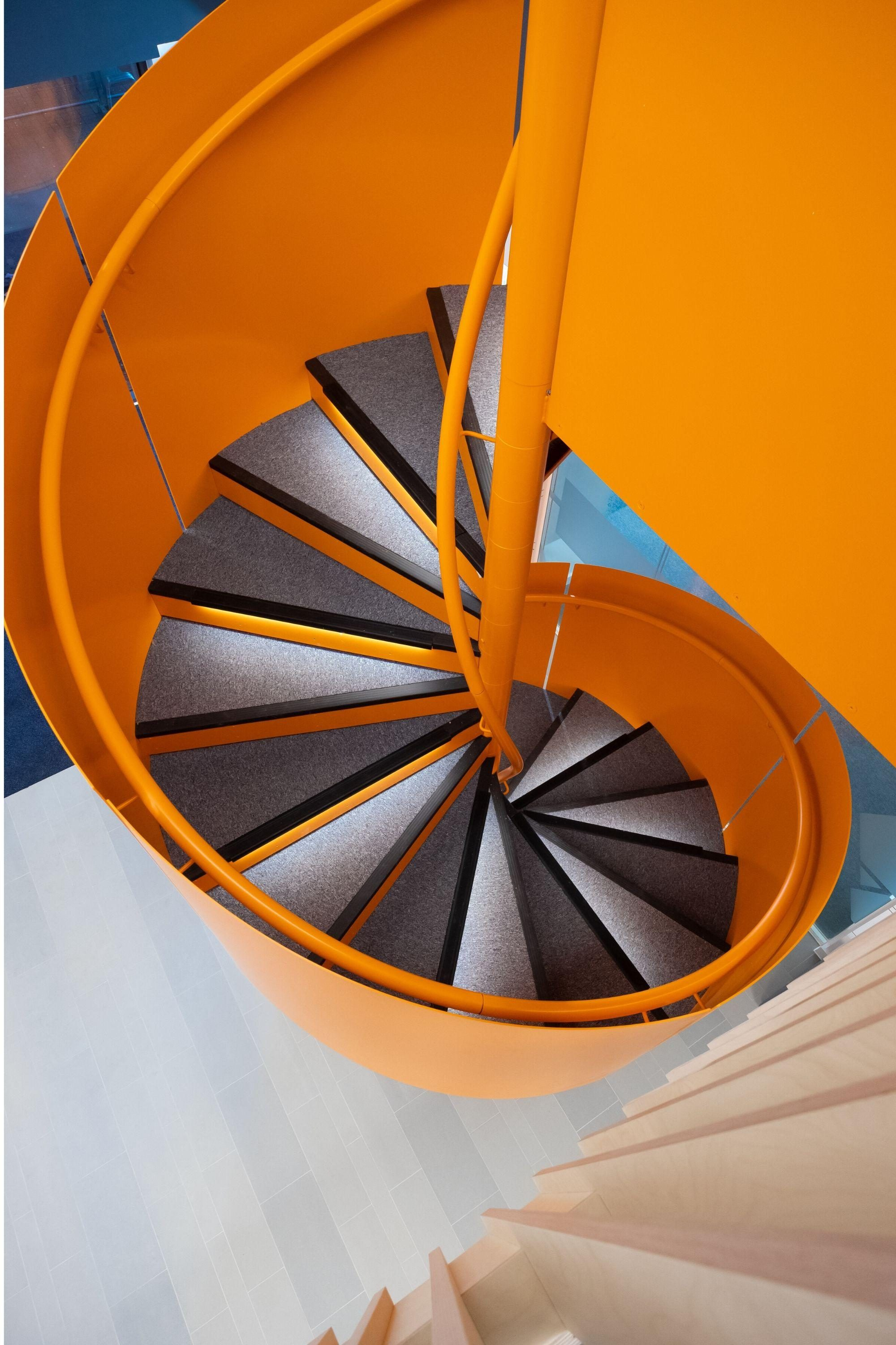 Orange balustrade and handrail on spiral stairs