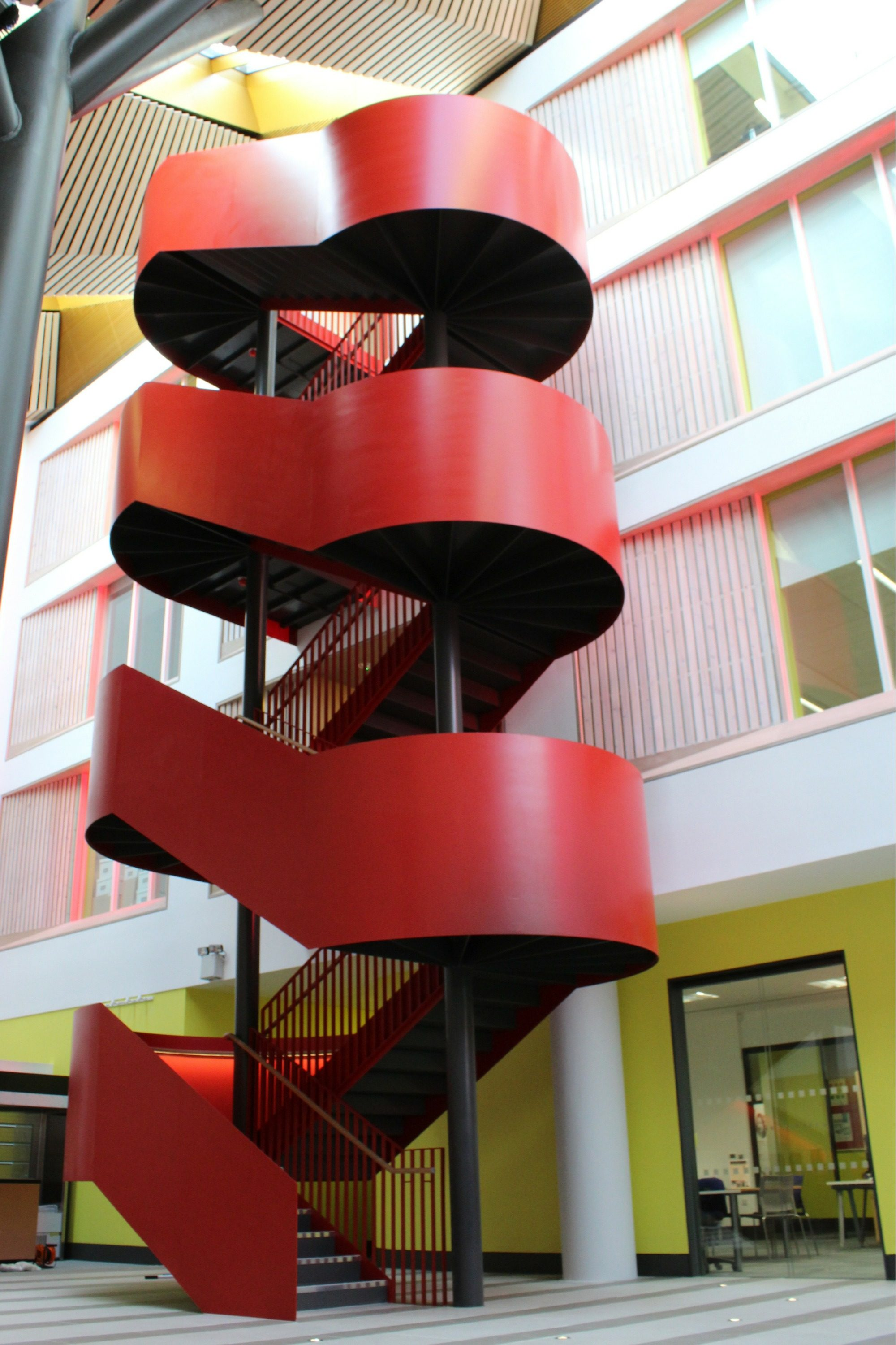 Striking helical staircase with red balustrade